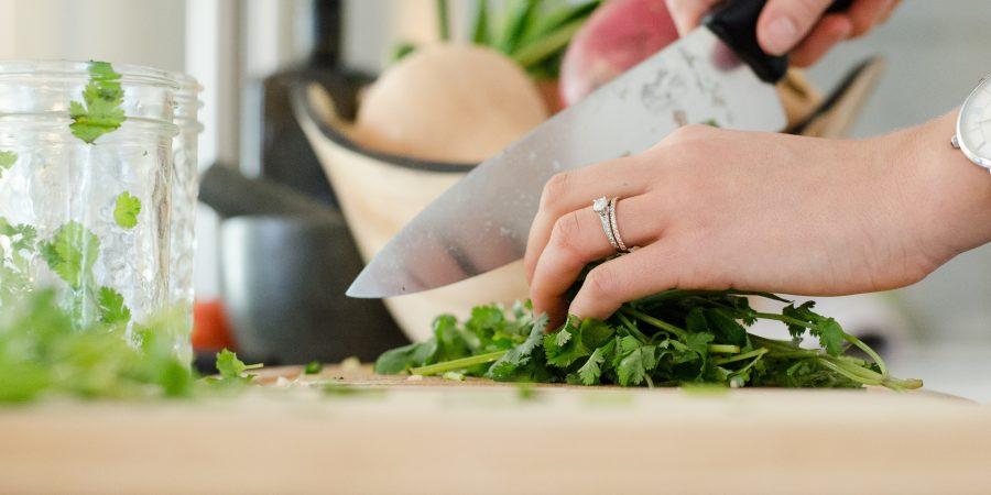 zoom sur les mains d'une personne qui coupe des herbes aromatiques avec couteau de cuisine sur planche à découper
