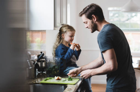 homme qui prépare à manger avec sa fille assise sur le comptoir à côté